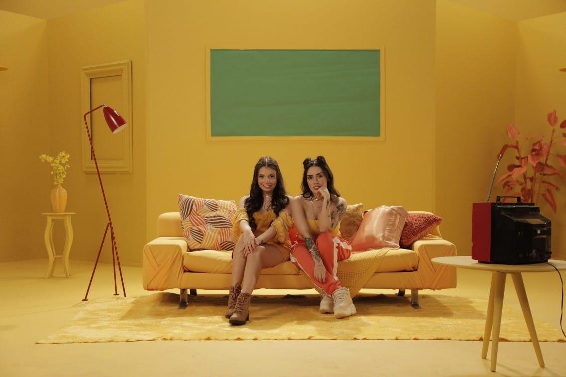 foto mostra as cantoras Carol e Vitória sentadas em um sofá